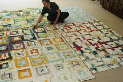 """Rossie Hutchinson is shown with three of her quilts.Together, they are the samples for a class she will be teaching at QuiltCon 2016 in mid-February.The class is called """"Intermediate Improv: Crosses, Cabins, and Colors."""""""