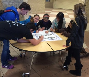 Students sign pledge that will hang on the wall in the hallway. Photo courtesy of Manchester High School.