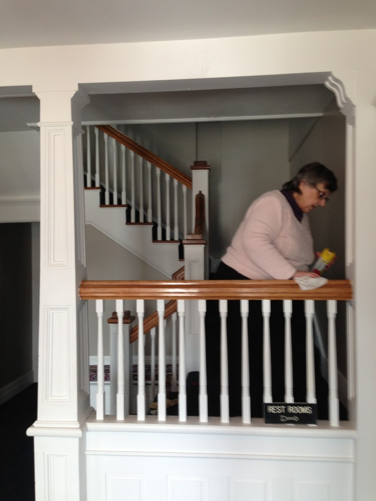 Sharon Curtis cleans the banister. Photo courtesy of the Manchester Area Historical Society.