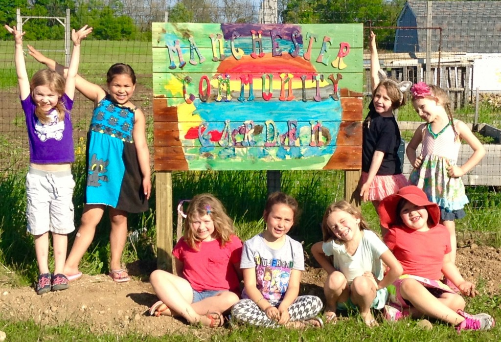 Eight of the troop of thirteen girls posing by the sign they designed, built, painted and installed at the Manchester Community Garden.