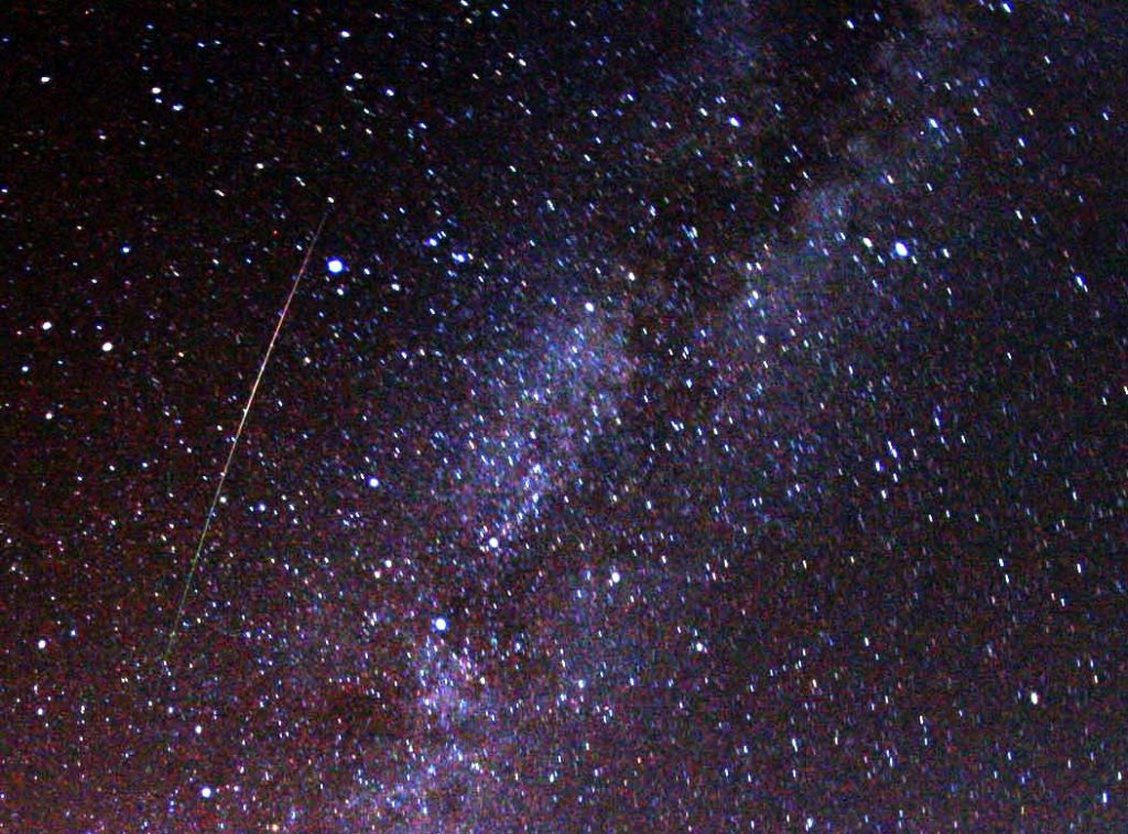 A multicolored, long Perseid meteor striking the sky just to the left of Milky Way.
