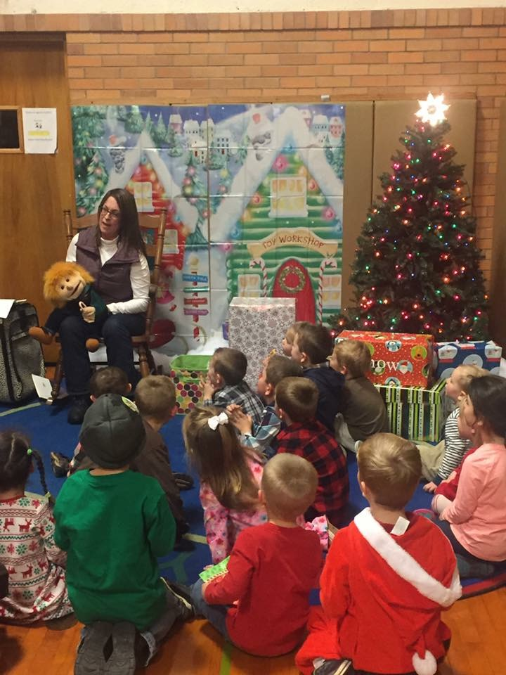 Mrs. Suzanne Birgy read a holiday story to the preschoolers following their program on Friday night.
